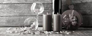 Para una cena romántica tenemos dos copas, una botella de vino, un par de velas y una caja de regalo