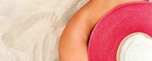 mujer nudista tumbada sobre la arena y que se tapa la cadera con un sombrero